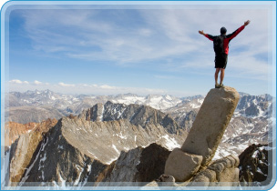 photo of man on a rock with arms outstretched