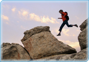 photo of person leaping from rock to rock