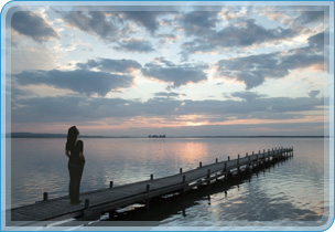photo of woman on jetty looking out over a lake